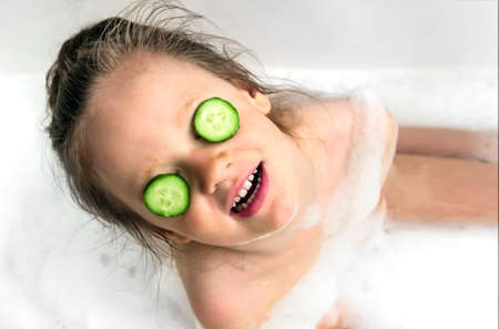 the girl smiles a snow-white smile in the bathroom face plastered with white cream and the eyes are a cucumber
