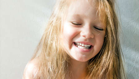 sur fond blanc belle fille brune aux cheveux noirs aux cheveux longs échevelés souriant teinte jaune éclairage rayons de soleil coucher de soleil aube matin Banque d'images
