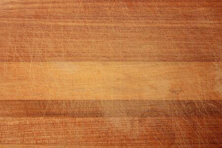 Textura de madera en rayones. La textura de la madera es de color naranja oscuro en los rayones. La textura de la tabla de cortar de madera con muchos rasguños del cuchillo.