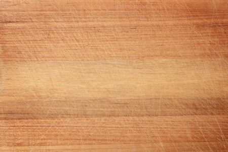 Wood texture in scratches. The texture of the wood is light orange in scratches. The texture of the wood cutting Board with a lot of scratches from the knife. Standard-Bild - 133658892