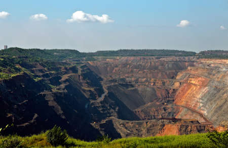 opencast mine obtains iron ore with tractors,trucks and diggers in sunny summer day photo