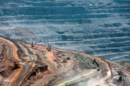 open cast mine: close up of quarry extracting iron ore with heavy trucks, excavators, diggers and locomotives Stock Photo