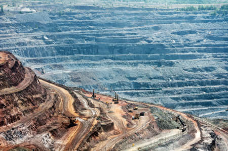 iron ore: close up of quarry extracting iron ore with heavy trucks, excavators, diggers and locomotives Stock Photo