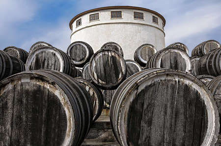 a lot of oak wine casks with madeira wine while maderization on solarium on blue clean a bit cloudy sky background photo