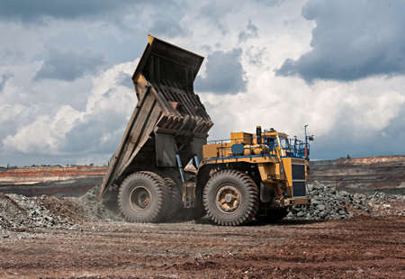 mining truck:  big yellow mining truck unload iron ore