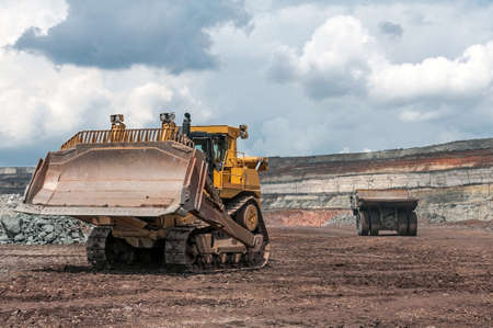 open cast mine: big yellow excavator and mining truck at worksite