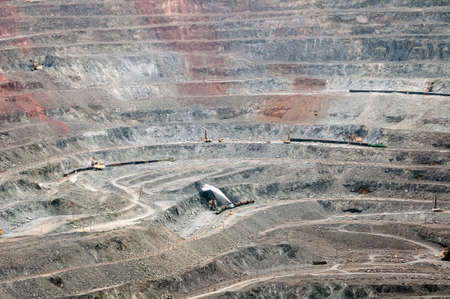 close up of quarry extracting iron ore with heavy trucks, excavators, diggers and locomotives photo
