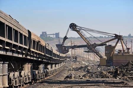 mining equipment: Excavator loading iron ore into goods wagon on the iron ore opencast mine