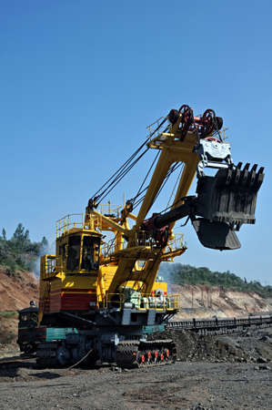 Excavator loading iron ore into goods wagon on the iron ore opencast mine photo