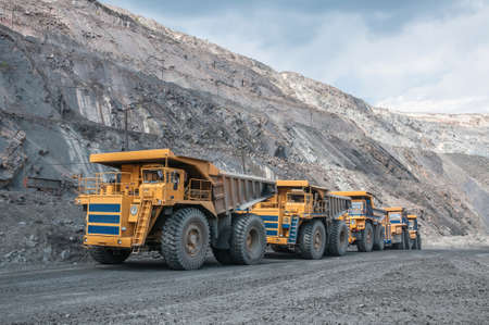 picture of big yellow heavy trucks in open cast mine Stok Fotoğraf