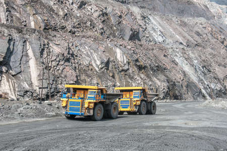 open cast mine: picture of big yellow heavy trucks in open cast mine Stock Photo