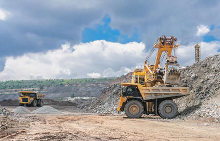 mining equipment: big yellow excavator extracting iron ore in opencast mine and loading heavy truck