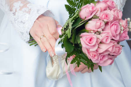 solemnization: close up of bride hand holding wedding bouquet of roses Stock Photo
