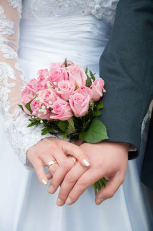 solemnization: close up of two  hands with wedding rings holding wedding bouquet of roses Stock Photo