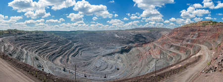 'earth mover': panorama of quarry extracting iron ore with heavy trucks, excavators, diggers and locomotives
