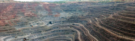 diggers: panorama of quarry extracting iron ore with heavy trucks, excavators, diggers and locomotives