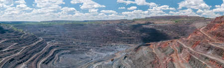 open cast mine: panorama of quarry extracting iron ore with heavy trucks, excavators, diggers and locomotives