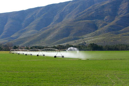 mechanical sprayers irrigating some fields near some mountains