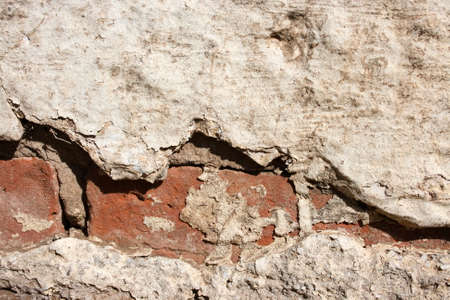broken old wall with plaster missing and bricks showing photo