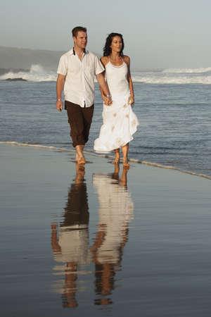 man and woman walking along the beach Stock Photo