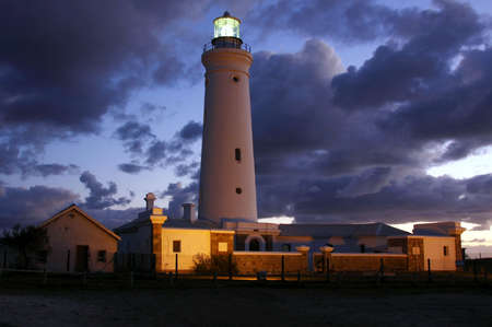 landscape view of a floodlit lighthouse with dark clouds at dusk