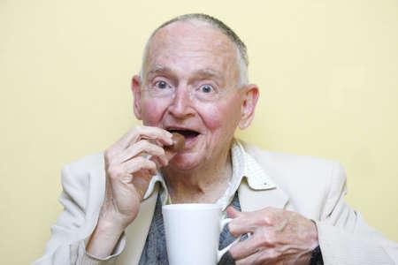 高齢男性コーヒーを飲みながら食べるチョコレート 写真素材