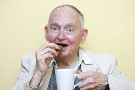 elderly man drinking coffee and eating chocolate