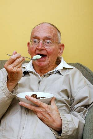 座っているといくつかのアイスクリームを楽しむシニア男性