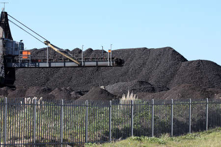 石炭の暗い黒の駒を移動する機械