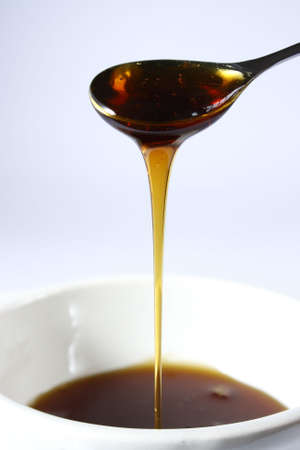 a spoon full of syrup being poured into a bowl
