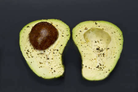Avocado pear sliced open with black pepper sprinkled on each side  Stock Photo - 20947688