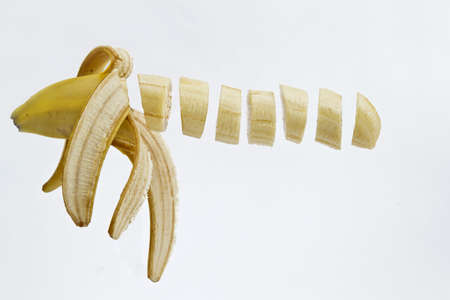 slices of banana in a row floating in mid air photo
