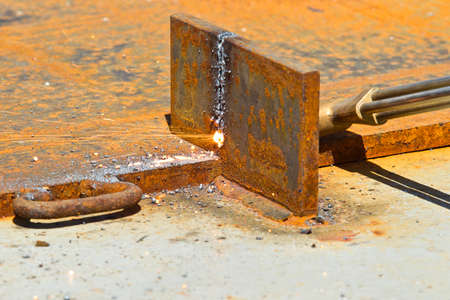 blow torch being used to cut through a thick piece of steel photo