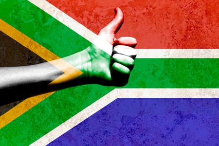thumbs up in a South African flag placed on a textured background Stock Photo