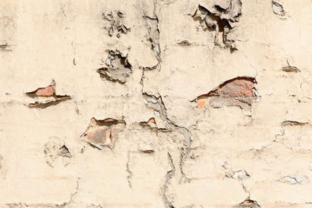flaking: old brick cracked brick wall with broken plaster and signs of decay Stock Photo