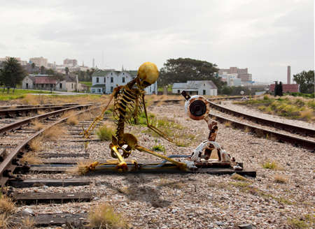 彼は到着する列車のための長い時間を待ったを示す鉄道信号で男の骨格