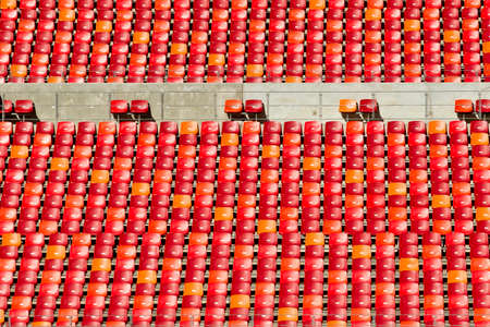 orange chairs: sport stadium chairs in large rows of red and orange