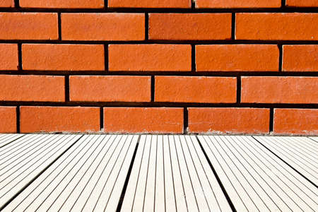decking: red brick wall background with some white decking leading up to it