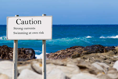 stating: seaside sign stating that one needs to be aware of strong currents and caution needs to be taken Stock Photo