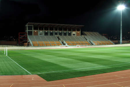 cut grass: sports stadium at night with bright flood lights and freshly cut grass