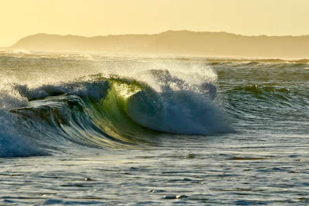 rolling landscape: large breaking waves with sea spray in the late afternoon sun Stock Photo