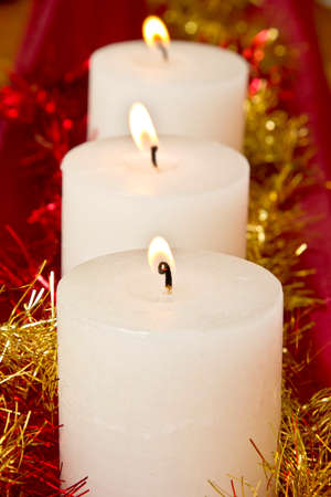 festivities: Candles in a row with bright tinsel showing festivities and celebrations