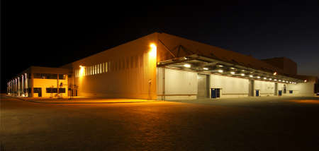 wide angle view of a modern warehouse at night in flood light light