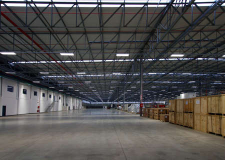 large interior of a modern warehouse with clean floors, and lots of racking Stock Photo