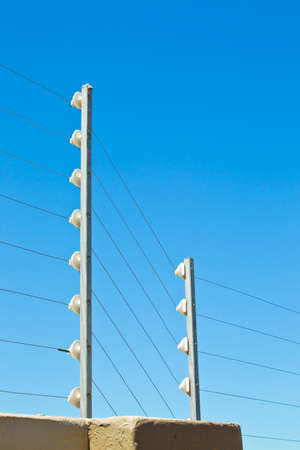 keepout: close view of long upright poles holding cables which are used to carry current for electric fencing Stock Photo
