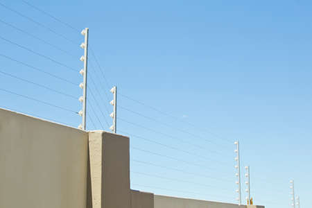 upright poles holding electric fencing cable on a boundary wall