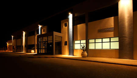 external view of a modern building at night with security floodlights burning