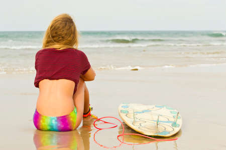 surfboard fin: Keen female surfer sitting on the sand looking out to sea for some waves Stock Photo