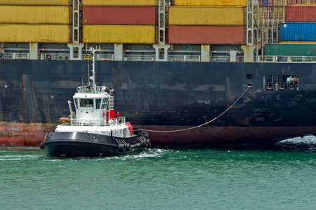 a tug boat moving a large container ship into place along side a harbor quay Stock Photo
