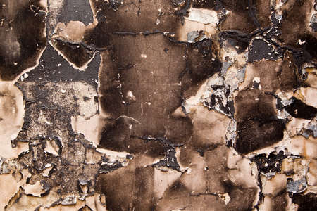 Dark grungy burnt wall with cracks and peeling paint